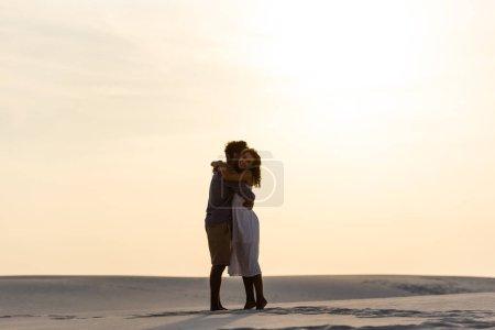 Photo pour Vue latérale de jeune couple étreignant sur la plage de sable au coucher du soleil - image libre de droit