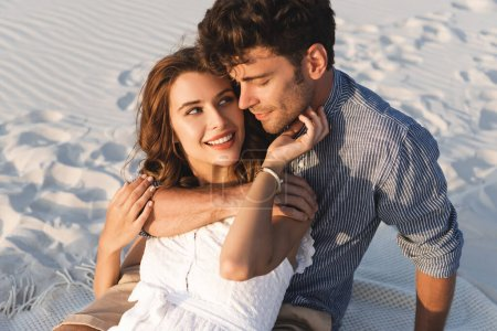 Photo for Smiling young couple hugging on beach - Royalty Free Image