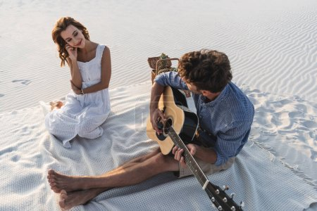 Photo for Man playing acoustic guitar to girlfriend on beach - Royalty Free Image