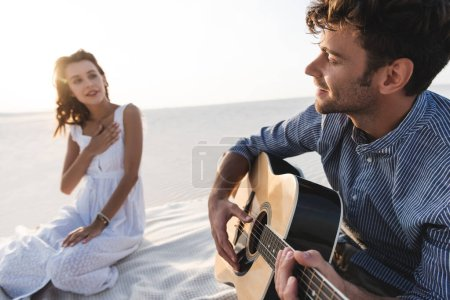 Photo for Selective focus of man playing acoustic guitar to girlfriend on beach - Royalty Free Image