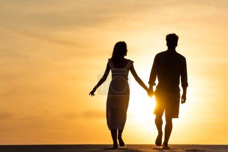 Photo pour Silhouettes d'homme et de femme se tenant la main tout en marchant sur la plage contre le soleil au coucher du soleil - image libre de droit