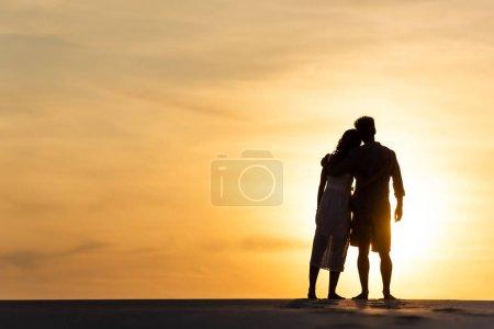 Photo pour Silhouettes d'homme et de femme étreignant sur la plage contre le soleil au coucher du soleil - image libre de droit