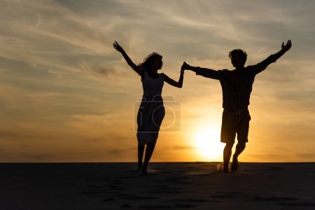 Photo for Silhouettes of man and woman running on beach against sun during sunset - Royalty Free Image