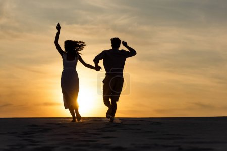silhouettes of man and woman running on beach against sun during sunset