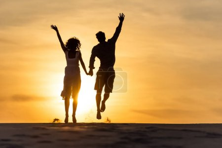 silhouettes of man and woman jumping on beach against sun during sunset