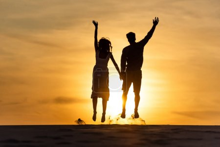 Photo for Silhouettes of man and woman jumping on beach against sun during sunset - Royalty Free Image