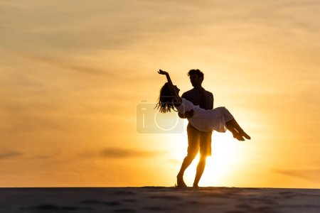 silhouettes of man spinning around woman on beach against sun during sunset