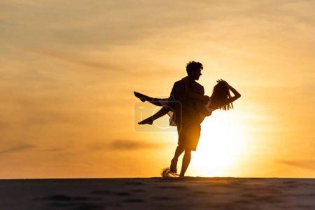 Photo pour Silhouettes d'hommes et de femmes dansant sur la plage contre le soleil au coucher du soleil - image libre de droit