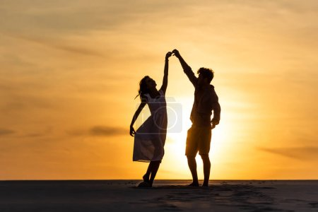 silhouettes of man and woman dancing on beach against sun during sunset