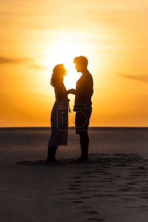 Photo for Side view of silhouettes of man and woman holding hands on beach against sun during sunset - Royalty Free Image