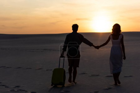 Photo for Back view of couple walking on beach while holding hands with travel bag at sunset - Royalty Free Image