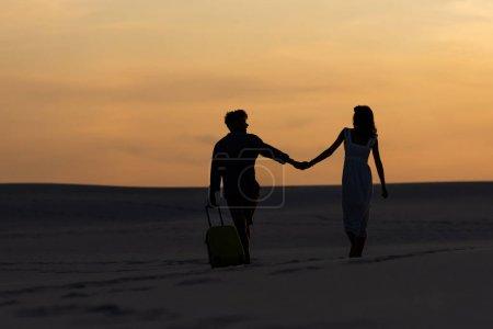 Photo pour Vue arrière du couple marchant sur la plage tout en se tenant la main avec un sac de voyage au coucher du soleil - image libre de droit