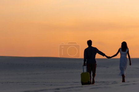 back view of couple walking on beach while holding hands with travel bag at sunset