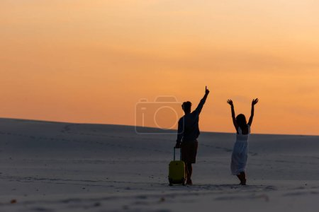 Photo for Back view of couple walking on beach with hands in air and travel bag at sunset - Royalty Free Image