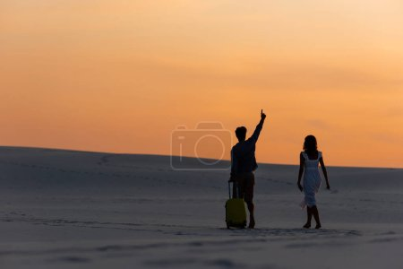 Photo for Back view of couple walking on beach with raised hand and travel bag at sunset - Royalty Free Image