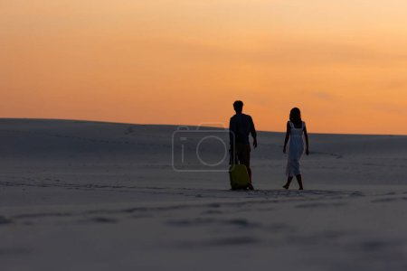 Photo for Back view of couple walking on beach with travel bag at sunset - Royalty Free Image