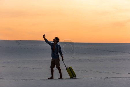silhouette of man walking on beach with travel bag and smartphone at sunset