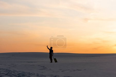Photo for Silhouette of man walking on beach with travel bag and smartphone at sunset - Royalty Free Image