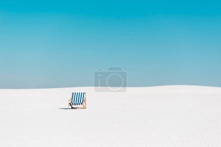 Photo pour Chaise longue vide sur la plage de sable contre un ciel bleu clair - image libre de droit