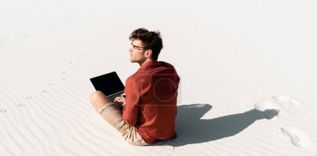 young freelancer sitting on sandy beach with laptop