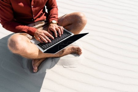 Photo pour Vue recadrée de jeune pigiste assis sur la plage de sable avec ordinateur portable - image libre de droit