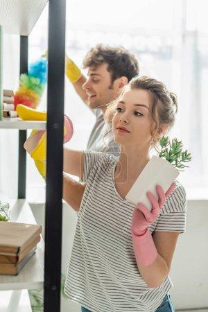 Photo pour Foyer sélectif de la fille attrayante dans des gants en caoutchouc tenant l'usine tout en nettoyant l'étagère avec chiffon près de l'homme - image libre de droit