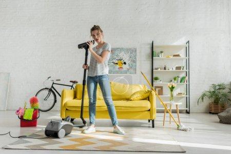 Foto de Atractiva mujer joven que mantiene aspiradora en el salón - Imagen libre de derechos