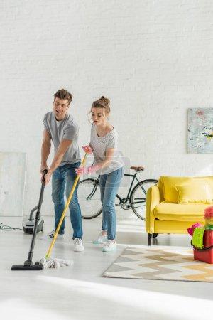 Photo pour Homme heureux en utilisant aspirateur près de femme attrayante plancher de lavage avec serpillière - image libre de droit
