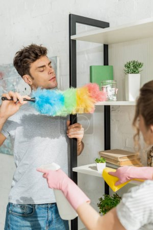 selective focus of handsome man cleaning shelve near girl