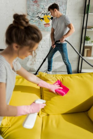 selective focus of handsome man using vacuum cleaner near girl washing sofa with rag