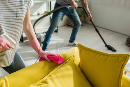 cropped view of woman holding rag and spray near sofa and man cleaning living room with vacuum cleaner