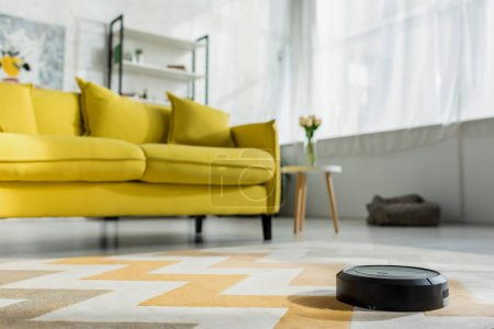 Photo for Selective focus of robotic vacuum cleaner washing carpet near sofa in living room - Royalty Free Image
