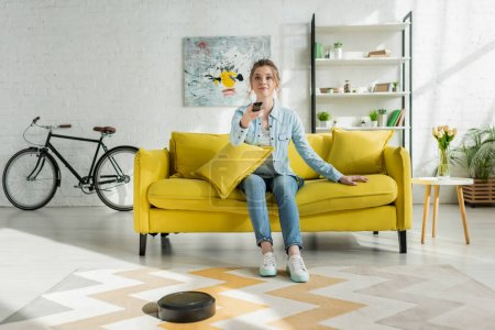 Photo pour Attractive woman watching tv while robotic vacuum cleaner washing carpet in living room - image libre de droit