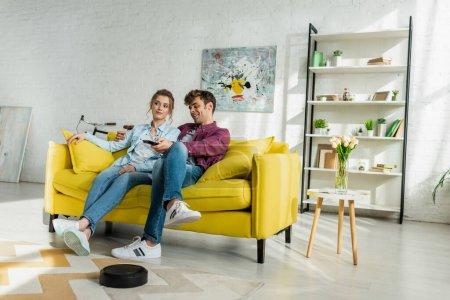 Photo pour Un homme heureux et une jeune femme regardant un film pendant un aspirateur robotisé laver un tapis dans un salon - image libre de droit