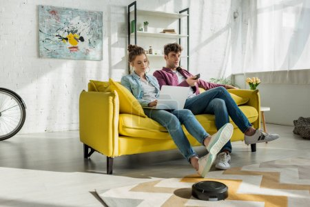 Photo for Man watching movie near woman using laptop while robotic vacuum cleaner washing carpet in living room - Royalty Free Image