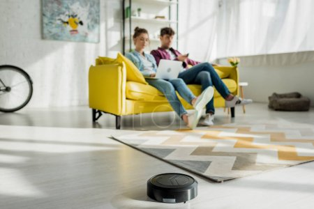 Photo for Selective focus of robotic vacuum cleaner washing carpet near man watching movie and woman using laptop in living room - Royalty Free Image