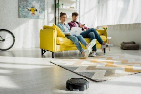 Foto de Enfoque selectivo de la alfombra limpiadora de vacío robótica cerca del hombre viendo películas y mujeres usando laptop en el salón. - Imagen libre de derechos
