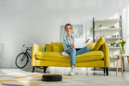 Photo for Attractive woman using laptop while robotic vacuum cleaner washing carpet in living room - Royalty Free Image