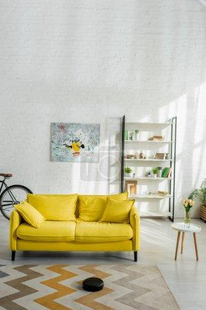 Staubsaugerroboter waschen Teppich in der Nähe von Sofa im modernen Wohnzimmer
