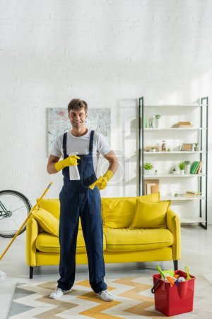 Photo for Happy cleaner in overalls holding rag and spray bottle in living room - Royalty Free Image