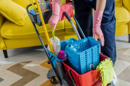 Photo for Cropped view of cleaner in rubber gloves standing near cleaning trolley - Royalty Free Image