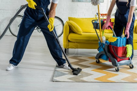Photo for Cropped view of cleaners in overalls cleaning apartment - Royalty Free Image
