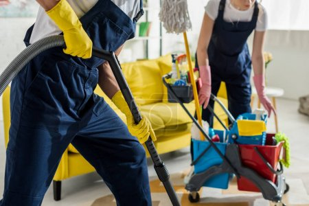 Photo for Cropped view of cleaners in overalls and rubber gloves cleaning apartment - Royalty Free Image