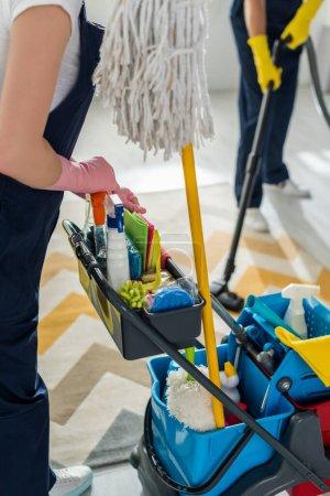 Foto de Vista de la limpieza en guantes de goma que se encuentran cerca de la carretilla de limpieza y de los trabajadores con aspirador más limpio. - Imagen libre de derechos