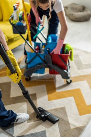 Photo for Selective focus of cleaner in rubber gloves standing near cleaning trolley and coworker with vacuum cleaner - Royalty Free Image
