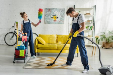 Photo for Young cleaners in overalls doing spring cleaning of modern living room - Royalty Free Image