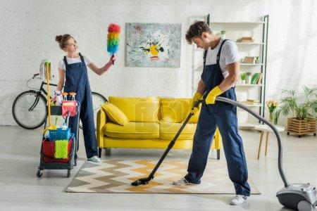 Photo pour Jeunes nettoyeurs en salopette faire le nettoyage de printemps de la salle de séjour moderne - image libre de droit