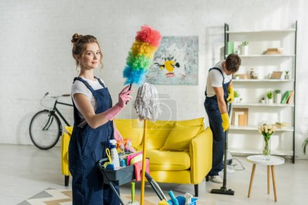 selective focus of young and happy cleaner holding duster brush near cleaning trolley