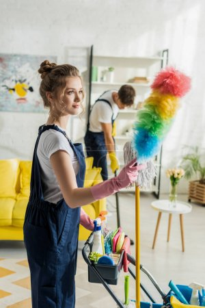 Photo for Selective focus of attractive cleaner holding duster brush near cleaning trolley - Royalty Free Image