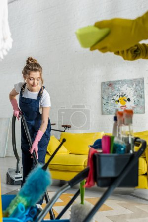 Photo for Selective focus of attractive cleaner using vacuum cleaner near coworker with sponge - Royalty Free Image